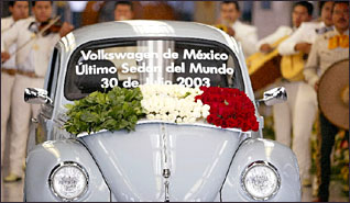 baby-blue vw bug, with flower garlands, serenaded by mariachi band