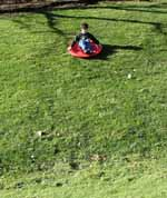 Kid on sled on snowless hill